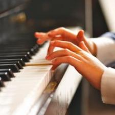 Child's hands playing piano are a result of pediatric hearing aids.