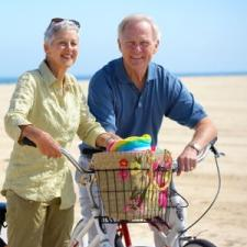 Couple on beach listen to in-the-ear hearing aid reviews.