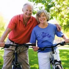 Couple on bikes consider hearing aid care.