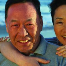 Having overcome relationship stress, couple hugs on beach.