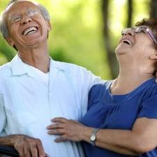 Couple laughs over hearing aid reviews of devices.