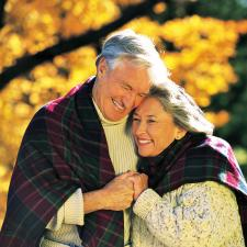 Happy couple with hearing aids hug in Autumn.