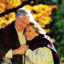 Man and woman cuddle under autumn leaves while considering where to purchase their hearing aids