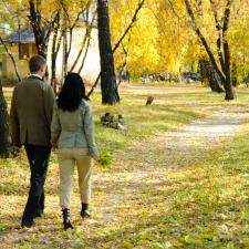 Couple walk in park discussing hearing loss causes.