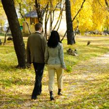 Couple walks on autumn trail, happy about the rising solutions of hearing loss.