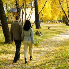 Couple on Autumn stroll ponders the consequences of ignoring hearing loss.