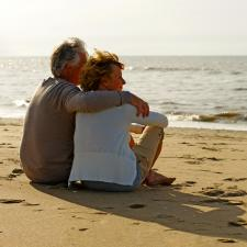Couple gaze out at ocean satisfied with the sound of their hearing aids.