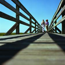 Couple stand together on long wooden pier.