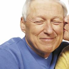 Elderly couple kisses to celebrate hearing and happiness.