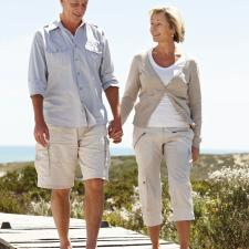 Couple walks on pier discussion hearing loss.