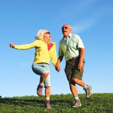 Couple outside jumping for joy at the benefits of a hearing aid..