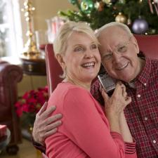 Man and wife listen to phone, slowly adjusting to the sound factor of each hearing aid.