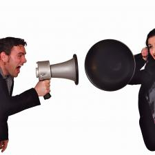 Man using bullhorn to communicate with woman holding trumpet to ear.