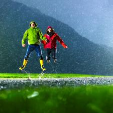 Couple jumps in rain to symbolize overcoming hearing loss.
