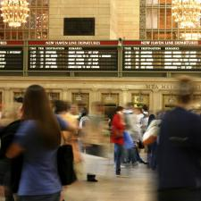 Blurry train station with commuters who should check their hearing.
