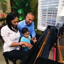 A family of three play the piano, thankful for the completely-in-the-canal hearing aid dad uses.