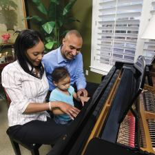 Child plays piano with family after learning of childhood hearing loss.