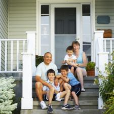Family sits on front porch steps.