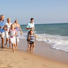 Family on vacation runs on beach unconcerned by father's hearing aids.