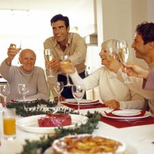 Family around table toasting. Hearing loss can make it difficult to understand conversations in a family setting.