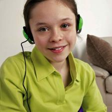Female student with headphones takes test for hearing loss.