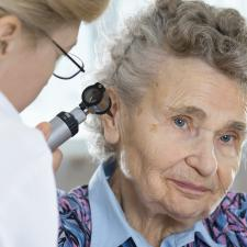 Doctor looks in patients ear to determine if she needs to upgrade her listening device.