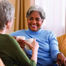 Two women on couch discuss the benefits of treating hearing loss