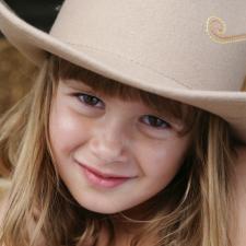 Little girl in cowboy hat. Children are sensitive to a parent's hearing loss.