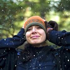 Female who knows signs and symptoms of hearing loss covers ears as snow falls.
