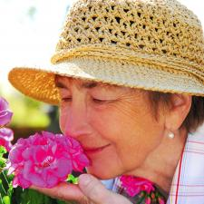 Senior smelling flower. Untreated hearing loss separates people from the sounds they love.