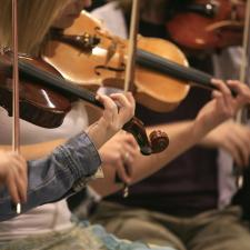 violins being played. Hearing music is a benefit of wearing a hearing aid