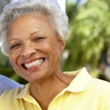 Woman smiling after upgrading her hearing aids
