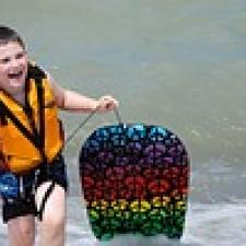 Child in surf protects his ears with earplugs.