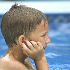 Child wearing waterproof earplugs. It's important to protect hearing during summer activities.