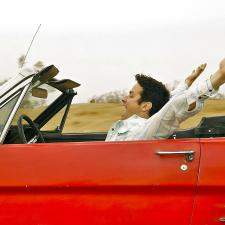 Man in red convertible throws up his hands, feeling free of hearing loss.