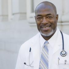 Male doctor smiles after helping patient with otosclerosis