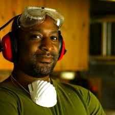 Man with goggles and ear protection is prepared for hearing loss in the workplace.