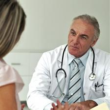 Male doctor with patient. Some people are confused about the difference between an audiologist and a hearing aid dispenser.