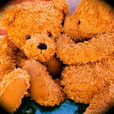 Teddy bears whispering about loud toys and childhood hearing loss.