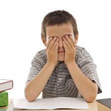 Child covers his eyes in frustration with his auditory processing disorder