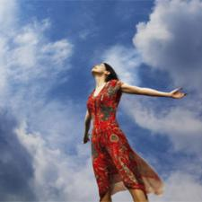 A woman stands under a blue sky, holding out her arms, taking joy in freedom from hearing loss.