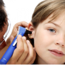 Doctor looks in girl's ear for signs of childhood hearing loss. Children with hearing loss are more likely to be bullied.