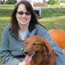 Sarah Wegley aka The Speak Up Librarian sitting on the grass with her dog Rusty.